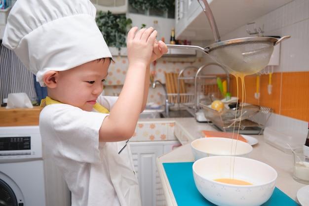 Netter asiatischer junge, der spaß beim kochen des frühstücks in der küche hat
