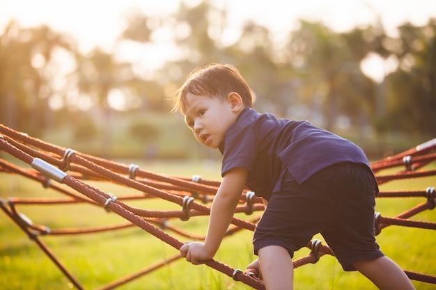 Netter asiatischer junge des kleinen kindes, der spaß hat, zu spielen und auf dem seil im spielplatz zu klettern