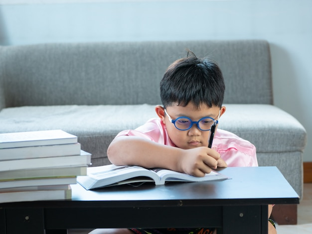 Netter asiatischer junge schreiben hausarbeit zu hause. bildungskonzept