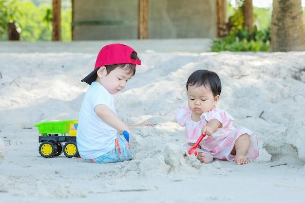 Netter asiatischer junge und mädchen der nahaufnahme spielen mit sand und spielzeug zusammen auf strukturiertem hintergrund des strandes