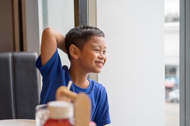 Netter asiatischer jungensitz am fenster lebensmittel in einem restaurant essend