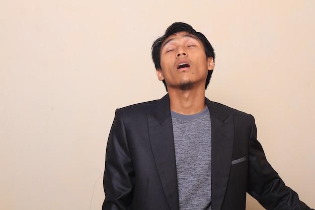 Netter asiatischer junger geschäftsmann, der bei der arbeit müde ist und schläft und trägt einen anzug mit einer strickjacke ins