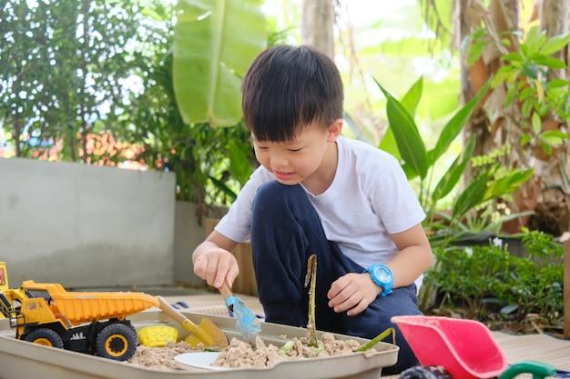 Netter asiatischer junger kindergartenjunge, der allein zu hause mit sand- und spielzeugbaumaschinen spielt