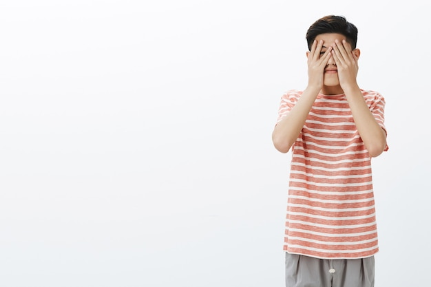 Netter asiatischer junger männlicher student, der gespannt ist, was das schicksal für ihn vorbereitet hat
