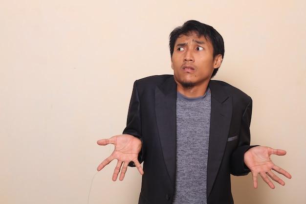 Netter asiatischer junger mann zeigt, dass ich geste nicht kenne, zuckte mit seinen schultern und trug a