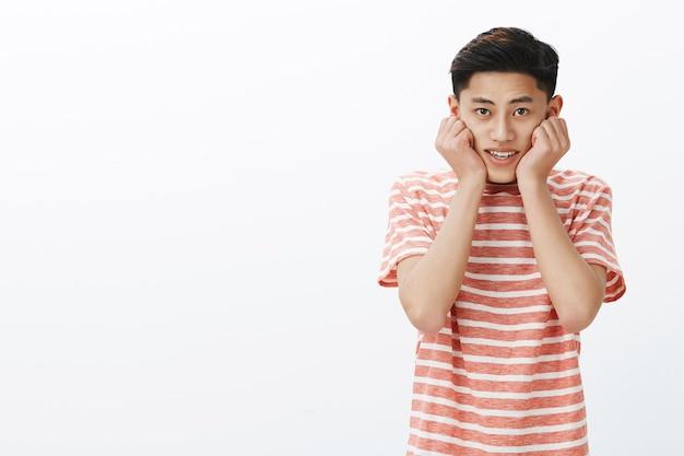 Netter asiatischer kerl, der mit bewunderung und interesse als das hören des lieblings-internet-bloggers schaut