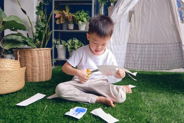 Netter asiatischer kindergartenjunge, der ein stück papier schneidet, scherenfähigkeiten für kleinkind einführen