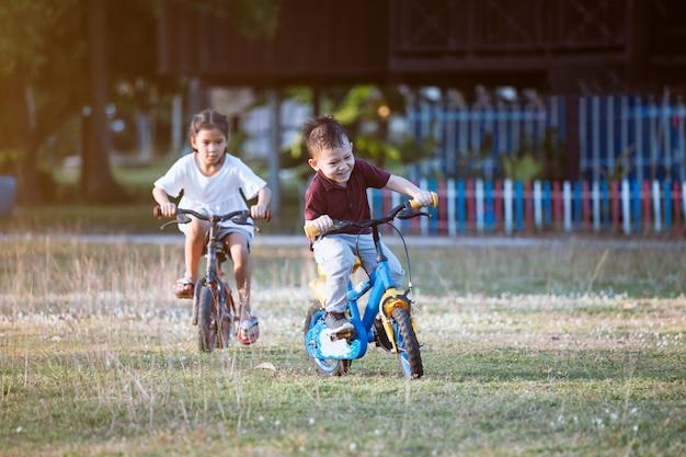 Netter asiatischer kinderjunge und seine alte schwester, die spaß hat, fahrrad im park zusammen zu fahren