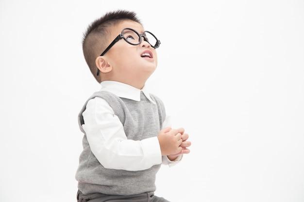 Netter asiatischer kleiner junge, der das weiße hemd, graue weste und gläser lokalisiert trägt. kreative ideen und innovationstechnologie-bildungskonzept