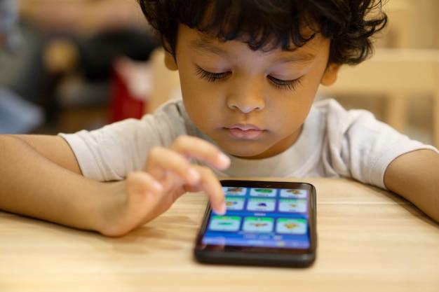Netter asiatischer kleiner junge spielt ein spiel auf smartphone