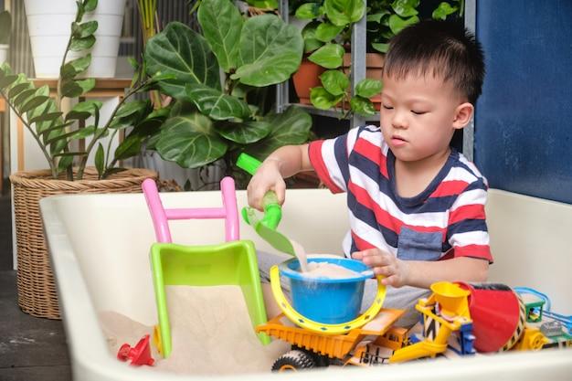 Netter asiatischer kleinkindjunge, der mit sand allein zu hause spielt, kind, das mit spielzeugbaumaschinen spielt, kreatives spiel für kinderkonzept