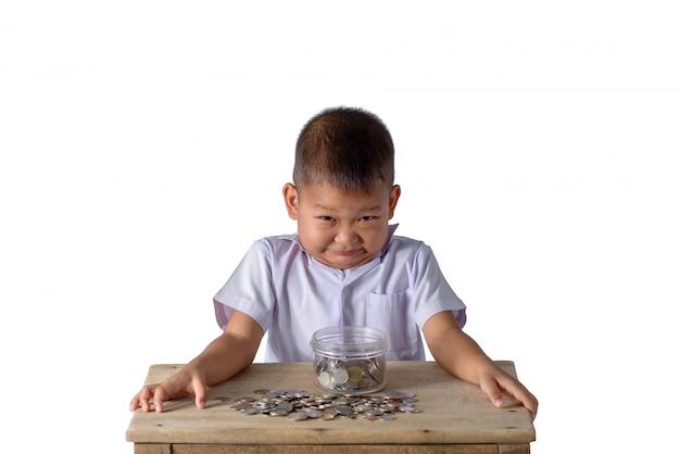 Netter asiatischer landjunge haben spaß mit münzen in der glasschüssel, die auf weiß lokalisiert wird