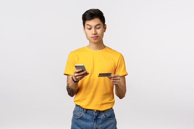 Netter asiatischer mann im gelben t-shirt, das smartphone und kreditkarte hält