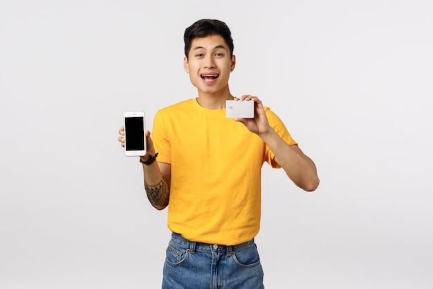Netter asiatischer mann im gelben t-shirt, das smartphone und visitenkarte hält