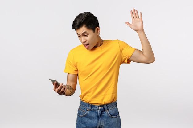 Netter asiatischer mann im gelben t-shirt, das smartphoneanzeige schaut, keucht und sich beschwert