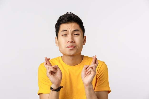 Netter asiatischer mann in den gelben t-shirt überfahrtfingern für gutes glück