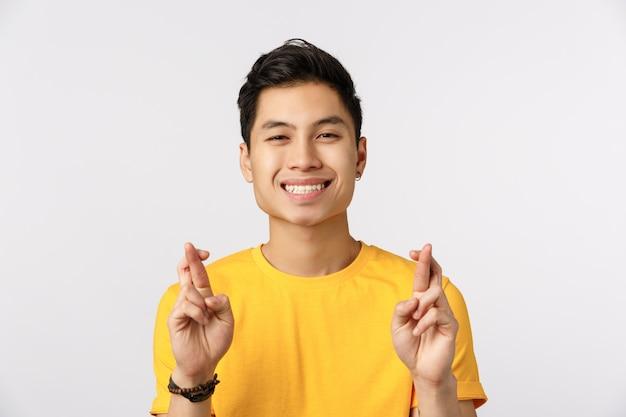 Netter asiatischer mann in den gelben t-shirt überfahrtfingern