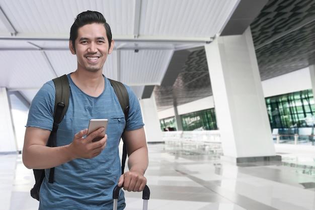 Netter asiatischer reisender mit rucksack unter verwendung des mobiltelefons