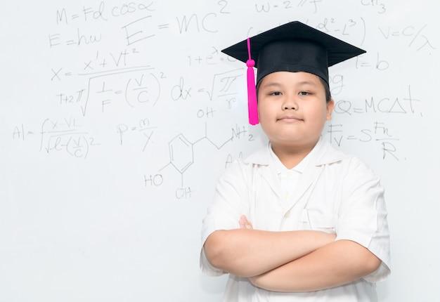 Netter asiatischer wissenschaftlerjungenabnutzungs-abschlusshut auf whiteborad mit wissenschaftlicher gleichung, wissenschaft und edu