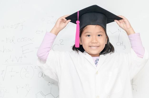 Netter asiatischer wissenschaftlermädchen-abnutzungs-abschlusshut lächeln auf weißem borad mit wissenschaftlicher gleichung, wissenschaft