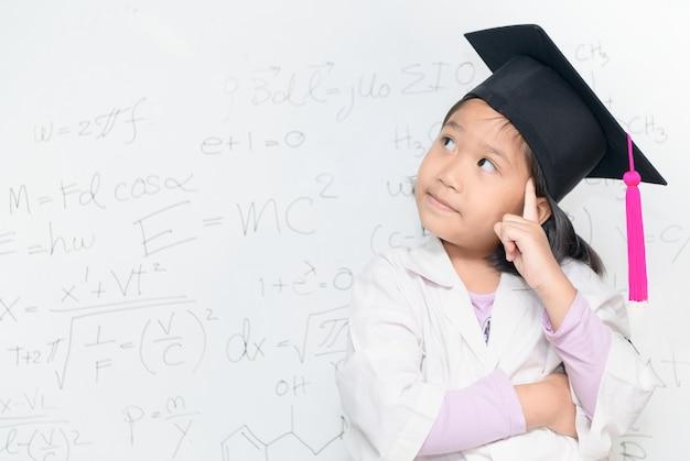 Netter asiatischer wissenschaftlermädchenabnutzungs-abschlusshut, der an weißem borad mit wissenschaftlicher gleichung, scie denkt
