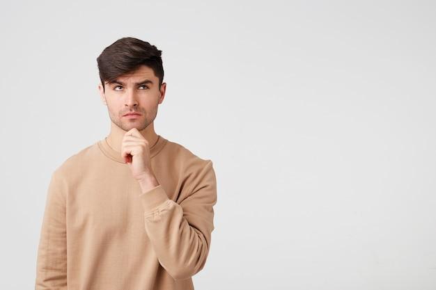 Netter attraktiver und charmanter mann mit borsten sieht nachdenklich aus