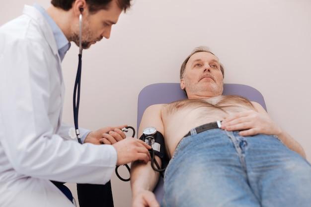 Netter aufmerksamer, angesehener arzt, der auf einem speziellen bett liegt, während sein arzt einige tests mit einem blutdruckmessgerät durchführt