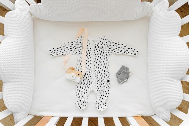 Netter babybody mit spielzeug. set kinderkleidung und accessoires. mode neugeborenes. flache lage, ansicht von oben