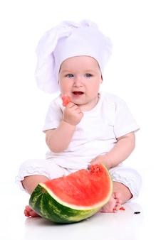 Netter babykoch mit wassermelone
