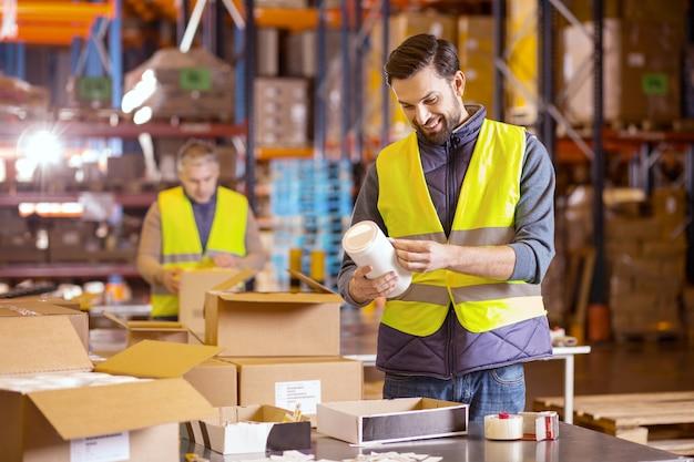 Netter bärtiger mann, der produkte während der arbeit im lagerhaus etikettiert