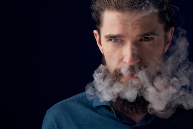 Netter bärtiger mann in hemd- und rauchmode dunklem hintergrund
