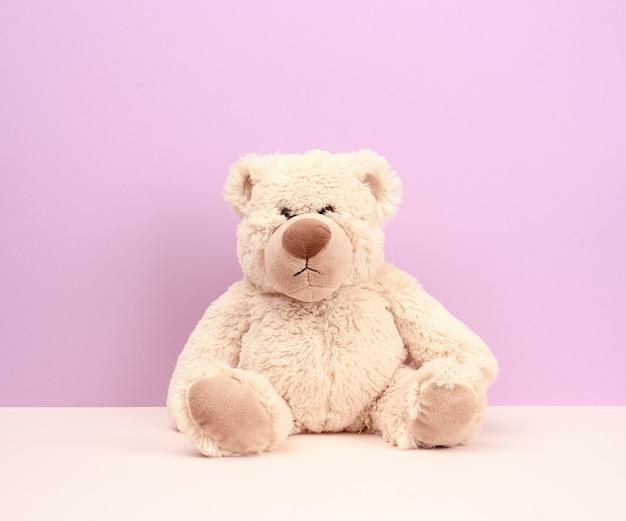 Netter beige teddybär, der auf lila hintergrund sitzt, traurig