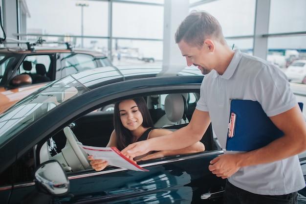 Netter berater steht am schwarzen auto und zeigt auf papier. in der anderen hand hält er eine plastiktafel. nette und junge frau sitzt im auto und schaut auf dokument.