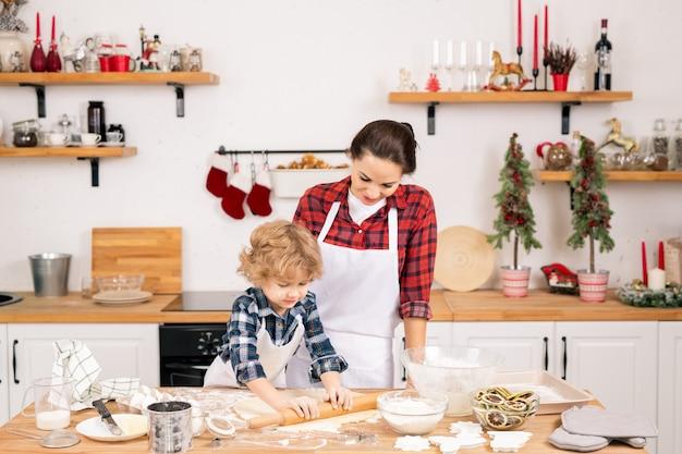 Netter blonder junge, der hausgemachten teig auf holztisch rollt, während seine mutter nahe beim kochen zusammen steht