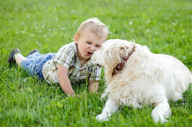 Netter blonder junge des kleinkindes mit golden retriever im freien