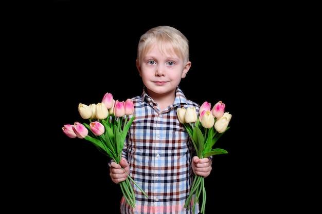 Netter blonder junge des porträts mit zwei blumensträußen von tulpen. muttertag-konzept