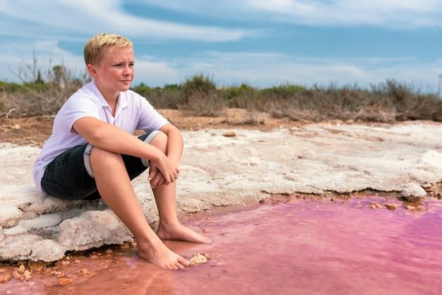 Netter blonder junge des teenagers, der sommerkleidung trägt, die am ufer eines erstaunlichen rosa sees sitzt