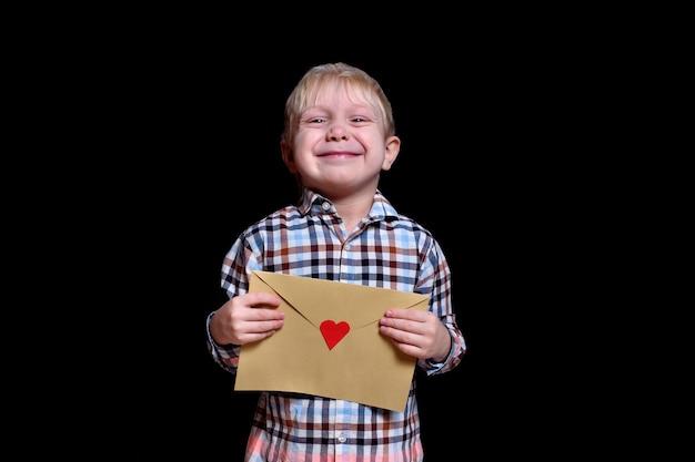 Netter blonder junge hält einen umschlag mit einem roten herzen. herzlichen glückwunsch zum valentinstag. schwarzer hintergrund