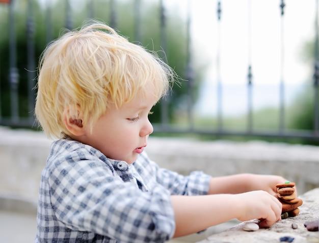 Netter blonder kleiner junge, der draußen mit kleinen steinen spielt. kleinkind kind baut turm
