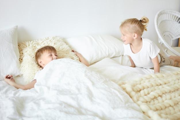 Netter blonder kleiner junge, der pyjamas trägt, der auf weißem großem bett sitzt und seinen älteren bruder weckt, der neben ihm schläft und guten morgen sagt. zwei brüder spielen zusammen im schlafzimmer und haben spaß