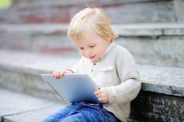 Netter blonder kleinkindjunge, der draußen mit einer digitalen tablette spielt. gadget für kleine kinder