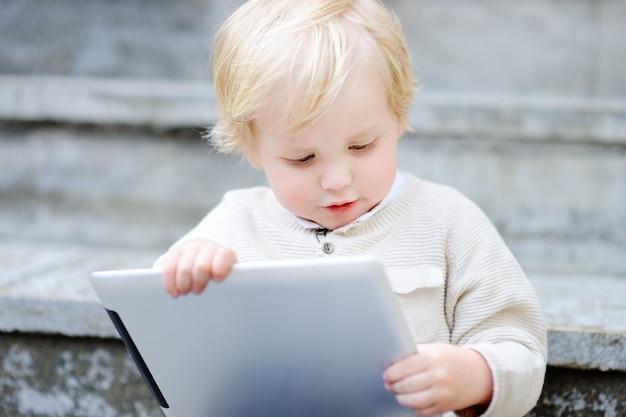 Netter blonder kleinkindjunge, der draußen mit einer digitalen tablette spielt