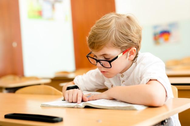 Netter blonder schüler mit stilvollen gläsern schreibend in klassenzimmer