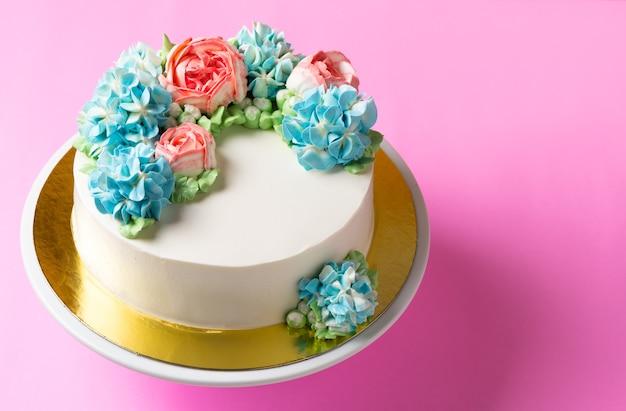 Netter blumenkuchen auf kuchenstand und hellrosa hintergrund, draufsicht