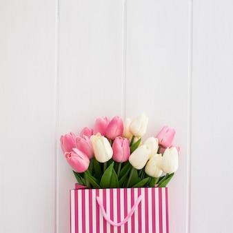 Netter blumenstrauß von tulpen innerhalb einer weißen und rosa tasche auf einem weißen hölzernen hintergrund