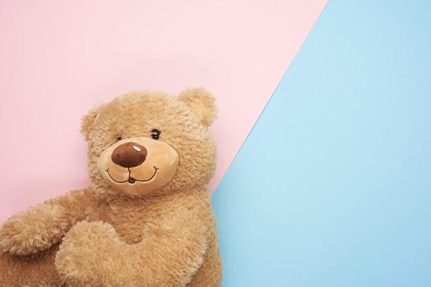 Netter brauner teddybär auf einem rosa-blauen hintergrund