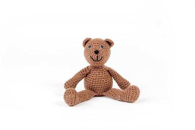 Netter brauner teddybär, der auf einer weißen oberfläche mit einem weißen hintergrund sitzt