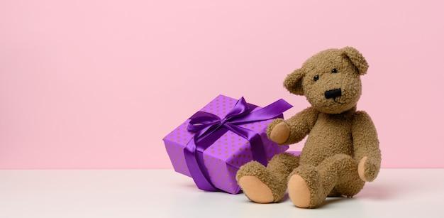 Netter brauner teddybär, der eine in papier und rotes seidenband eingewickelte schachtel auf weißem tisch hält. preis und glückwünsche, rosa hintergrund, kopienraum