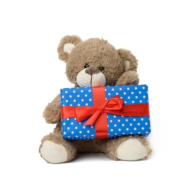 Netter brauner teddybär, der eine schachtel in blauem papier und rotem seidenband auf weißem, isoliertem hintergrund hält. preis und glückwünsche