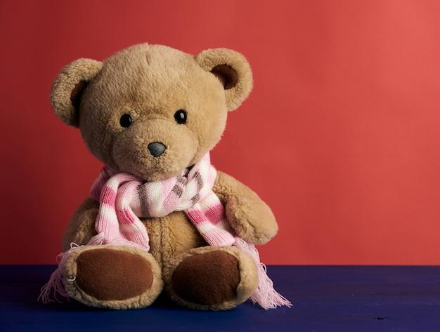 Netter brauner teddybär in einem farbigen gestrickten schal, der auf einem roten hintergrund sitzt